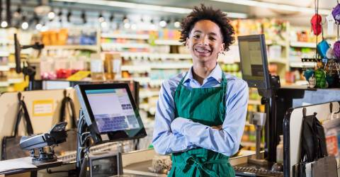 Tiener jongen werkt in supermarkt als kassier